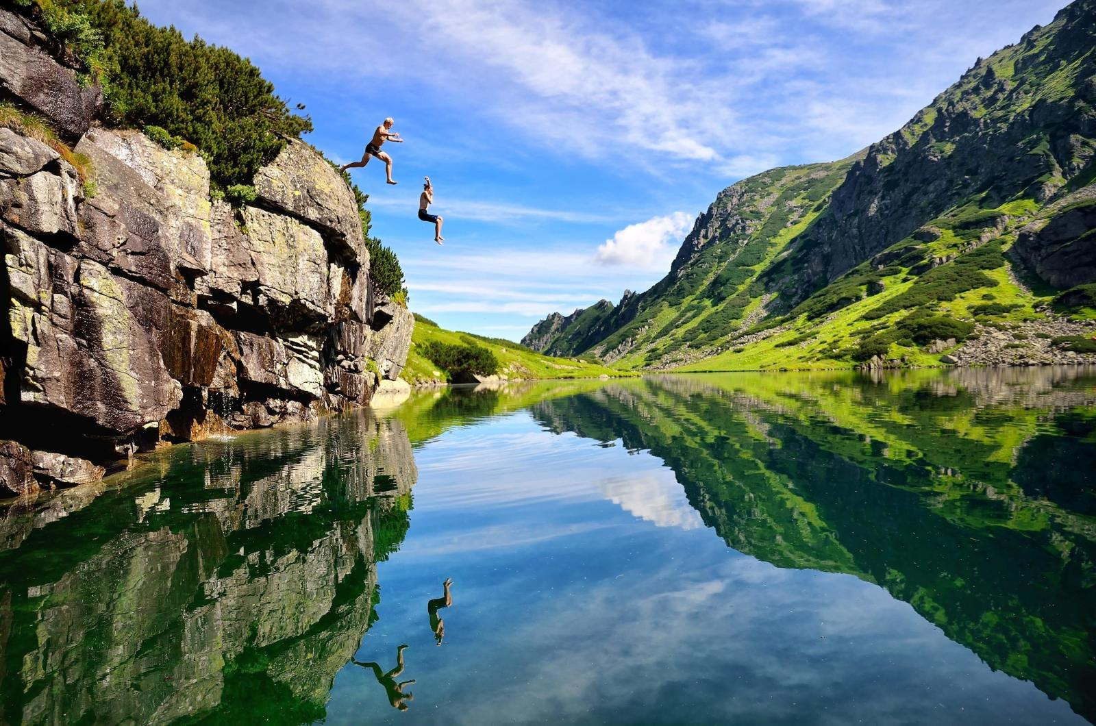 Two travellers enjoy their adventure by jumping off a cliff into water